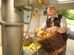 Toni Lassacher (Obmann Obst- und Gartenbauverein) füllt Äpfel in die Saftpresse c Rita Newman