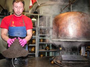 Adi Peermann setzt den Hut auf die Holzform auf, nachdem er den Rohling erst fuenf Minuten im Kessel bedampft hat.