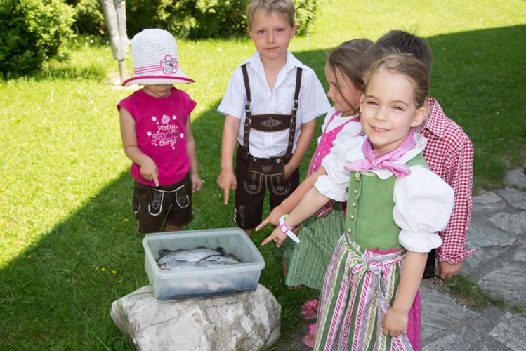 Die Kinder nehmen die Forellen unter die Lupe.