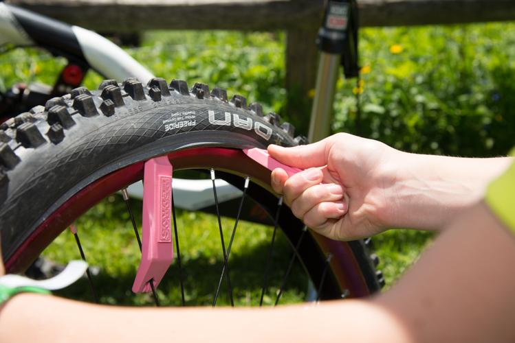 ... den ersten Reifenheber in der Nähe des Ventils einsetzen und an der Speiche fixieren. Mit dem zweiten Reifenheber den Mantel abziehen.