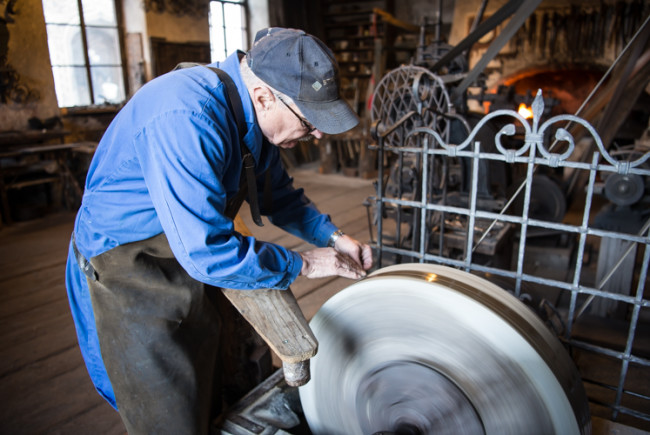 Adam Grundner schäft das Messer am wasserbetriebenen Naturstein.