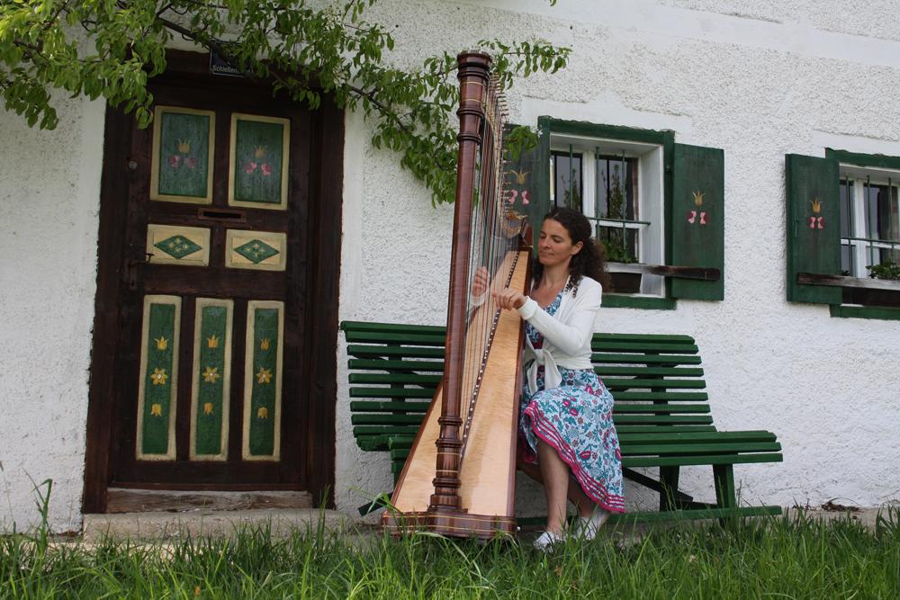 Heidi Pixner mit Harfe auf der Hausbank beim alten Bauernhaus
