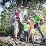 Oma und Opa mit Kindern an der Schautafel von Tillys Waldpfad