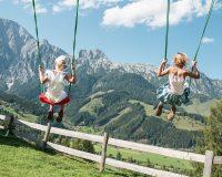 SChaukelnde Kinder vor der Aussicht auf die Bergwelt von Saalfelden Legoang