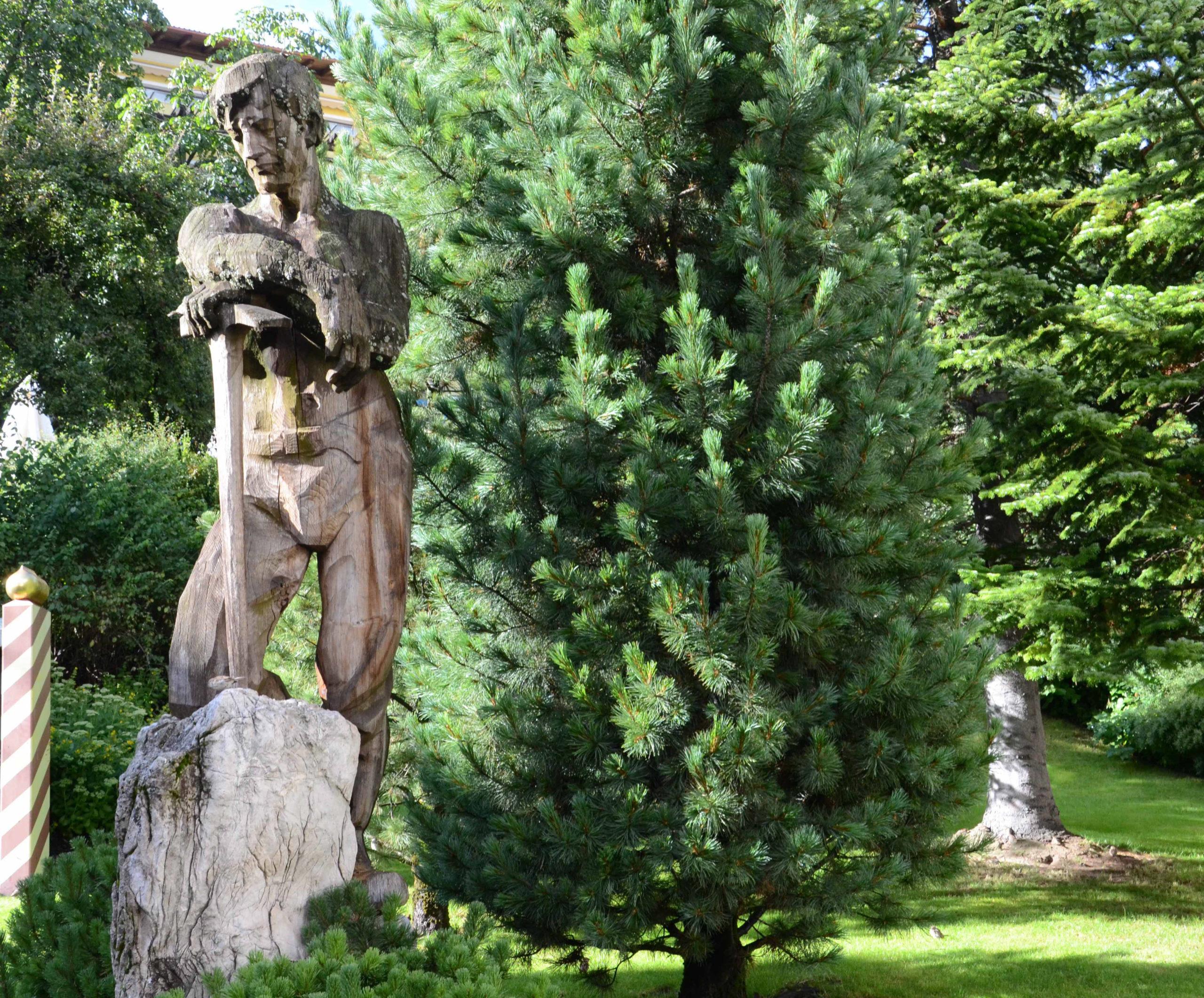 Statue in einem Garten mit Dolomitgestein und Zirbe