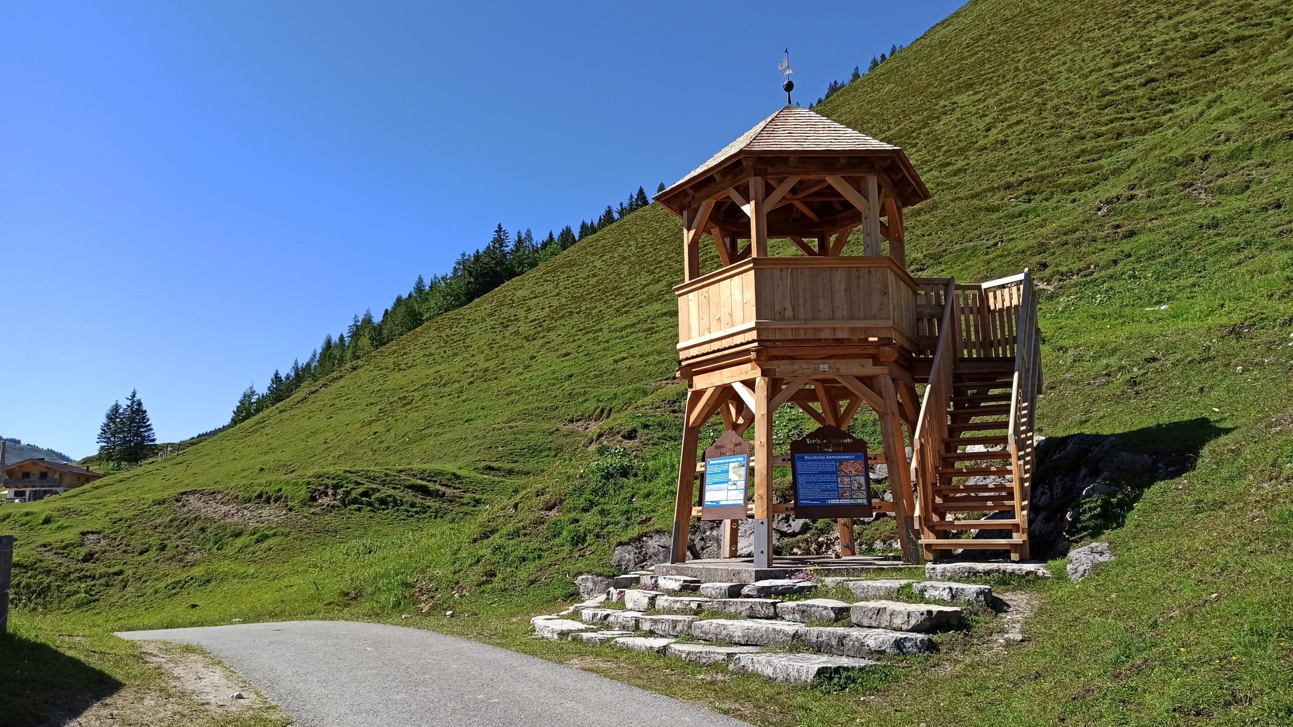 Der kleine Aussichtsturm unmittelbar am Radweg, dahinter der steile Hang