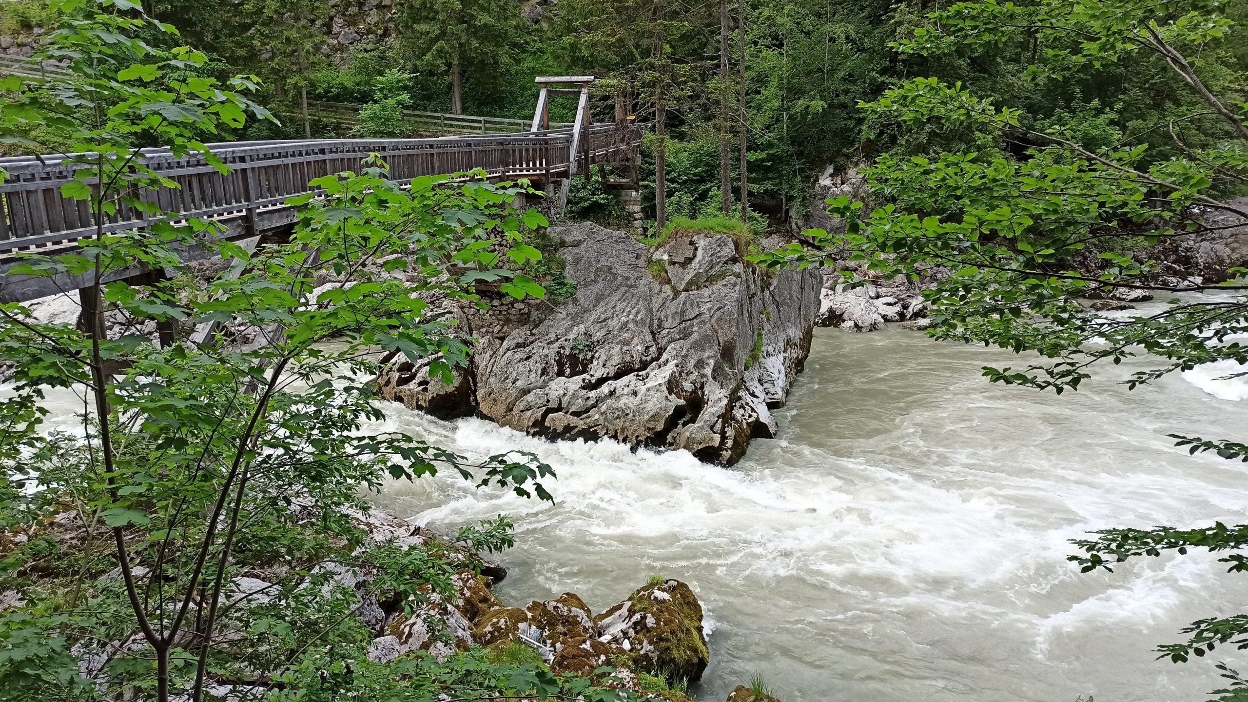Über wildem Wasser und massivem Felsen überqueren wir die prächtige Holzbrücke