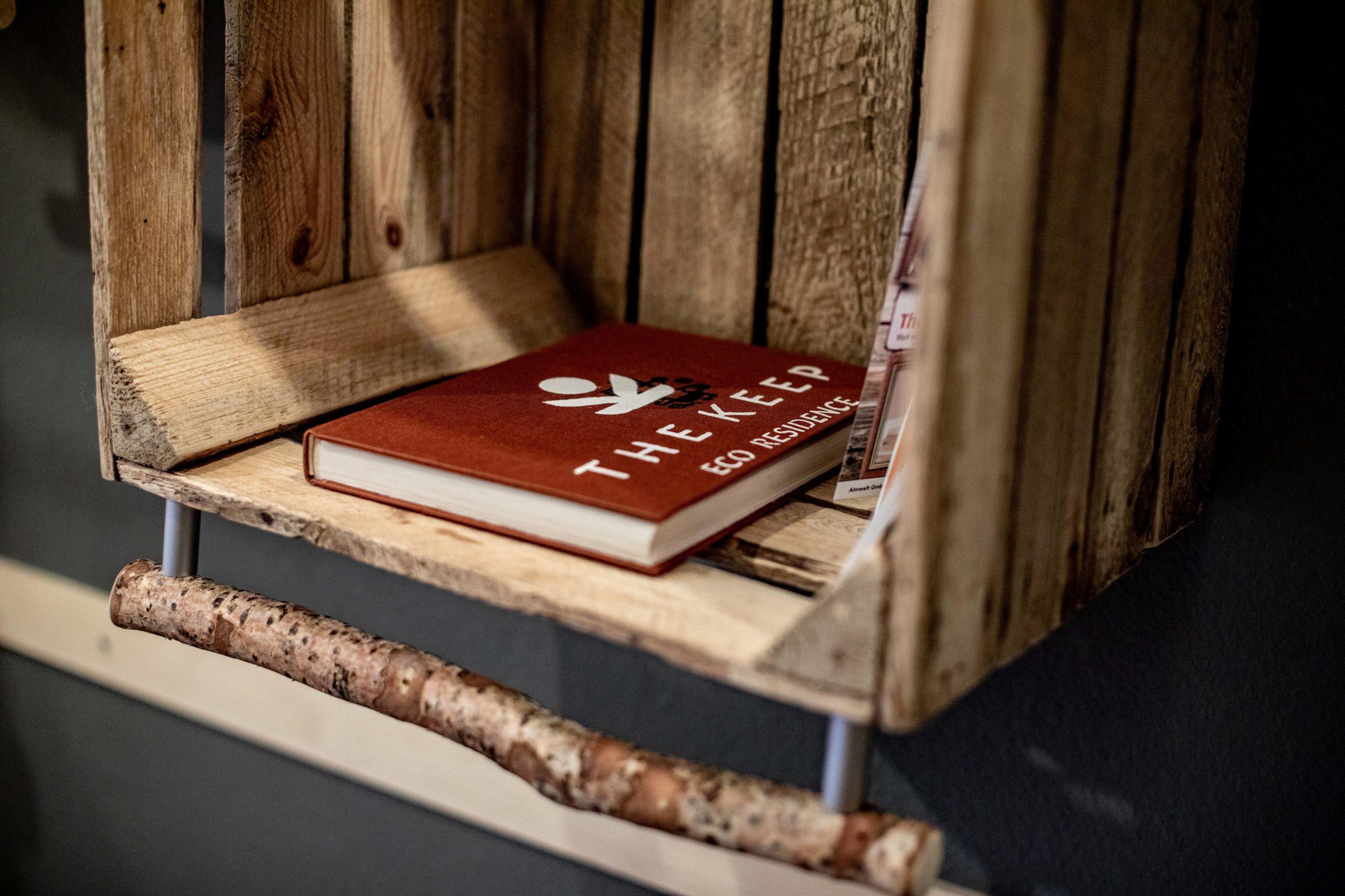 The Keep Bibel mit Nachhaltigkeitsphilosophie im Regal aus Obstkisten.  (c) wildbild