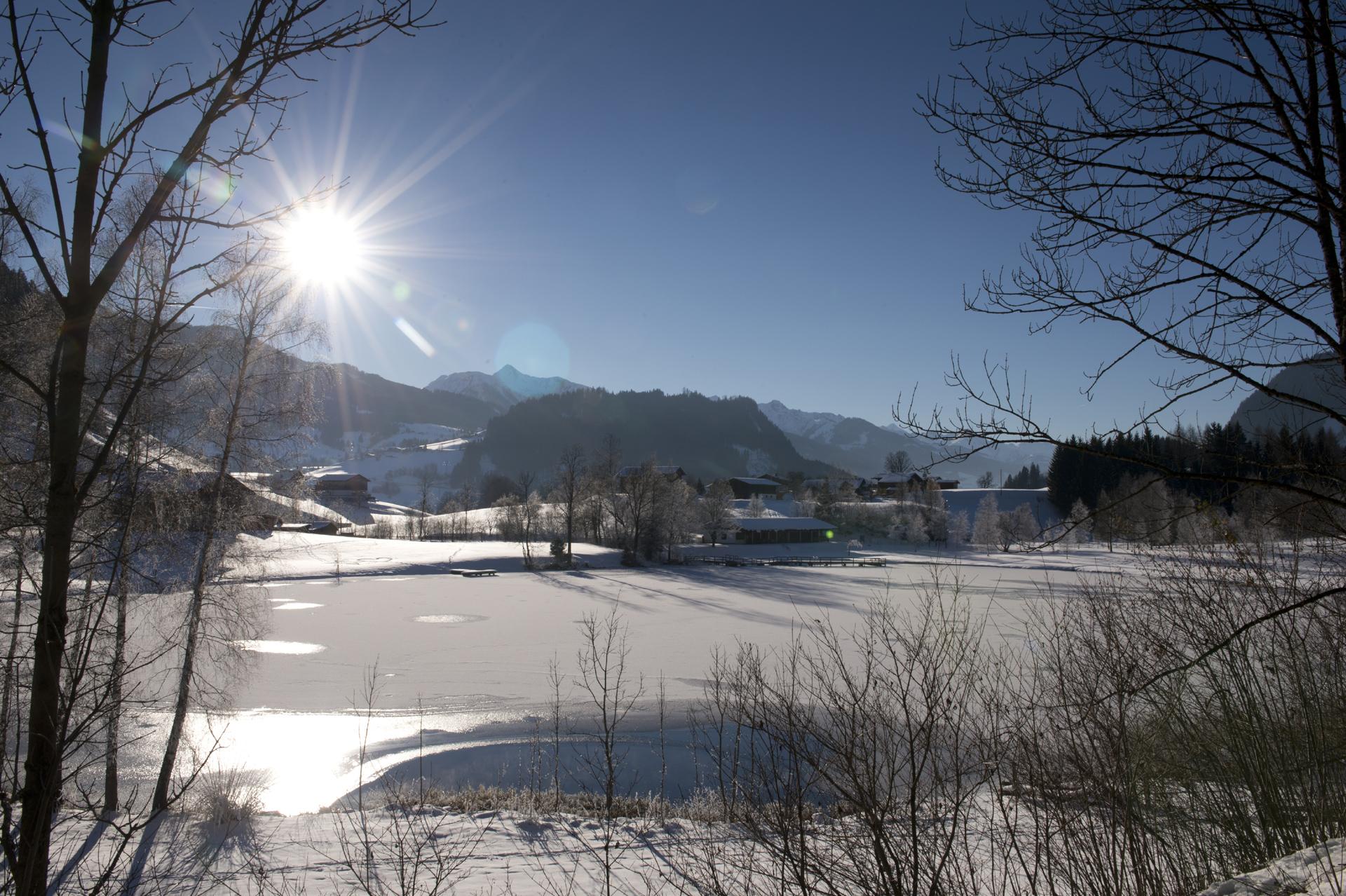 Zugefrorener Böndlsee in Goldegg im Sonnenschein
