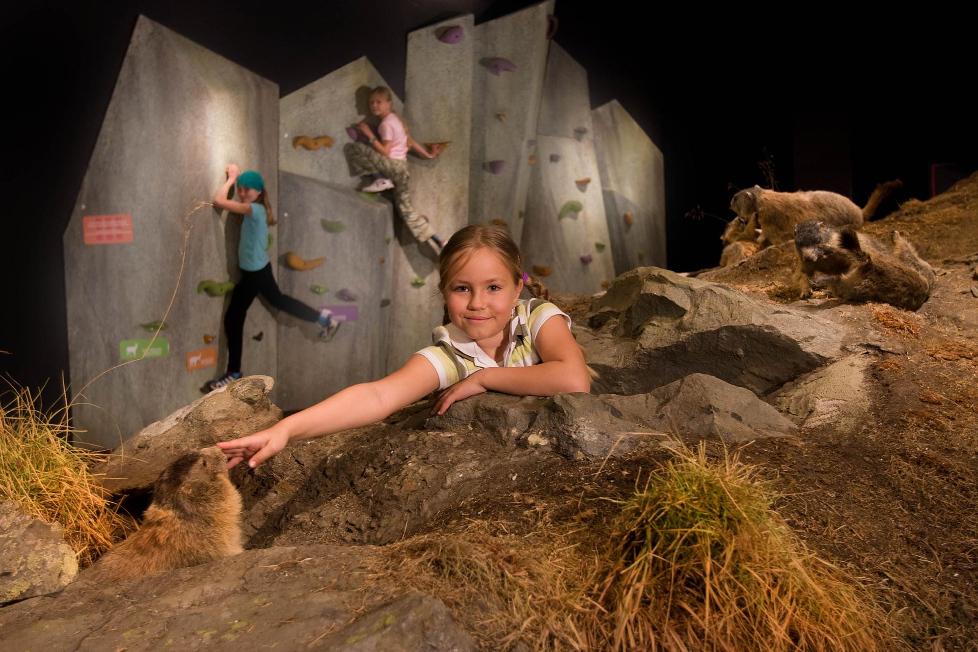 Kinder im überdimensionaklen Murmeltierbau, im Hintergrund eine Kletterwand