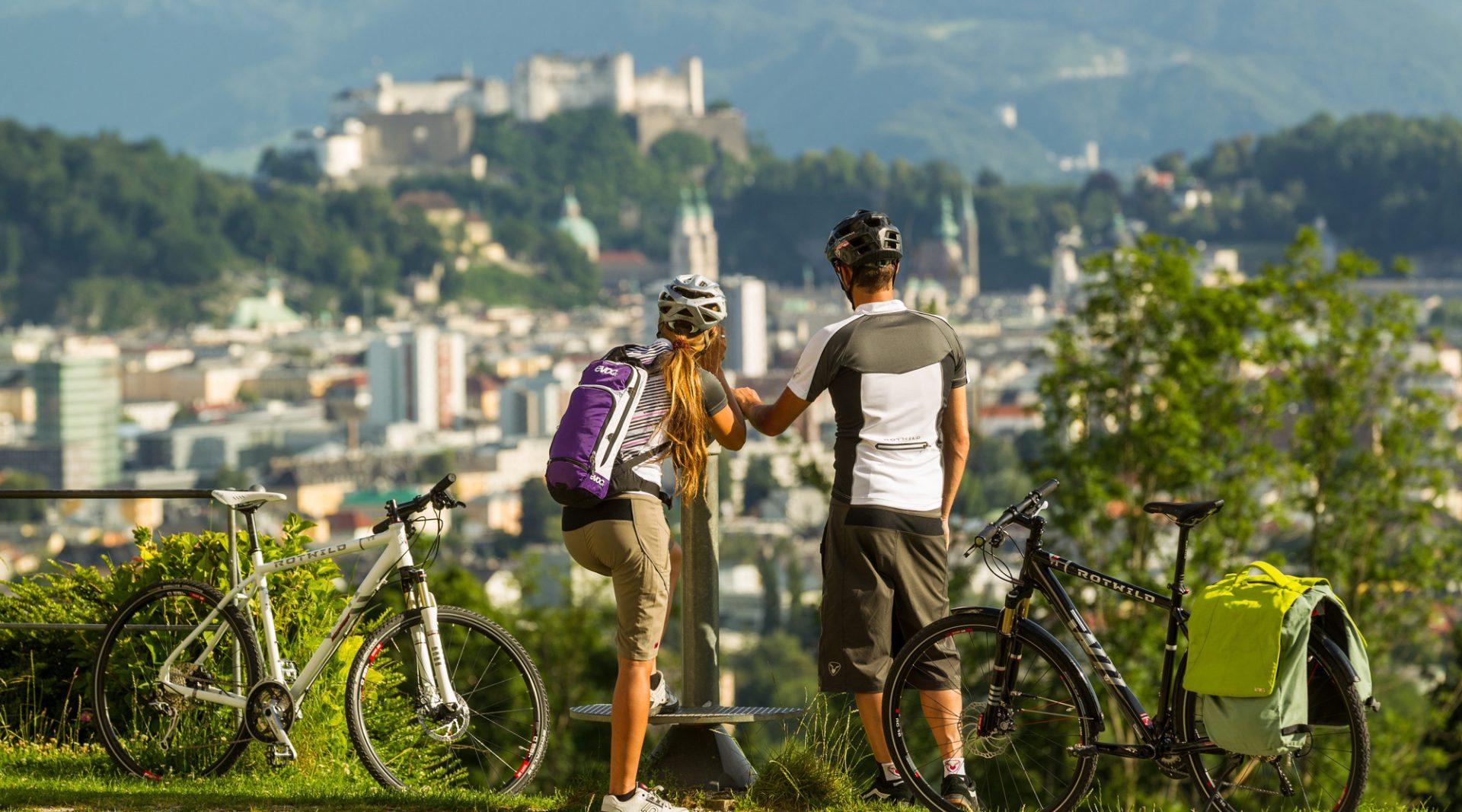 Ein Pärchen steht neben den Fahrrädern und genießt den imposanten Blick auf die Stadt Salzburg, einer der Höhepunkte am Tauernradweg.